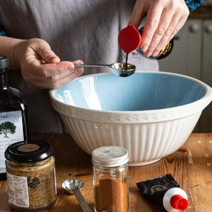 woman in grey pouring soy sauce from a bottle into a measuring spoon over a blue mixing bowl