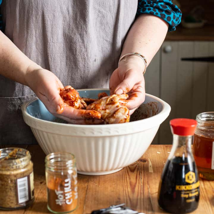 womans hands mixing raw chicken wings with a sticky honey based marinade in a blue and white mixing bowl