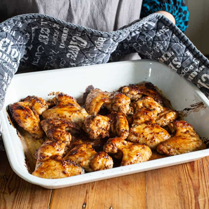 womans hands in black and white oven gloves holding a hot tray of sticky chicken wings