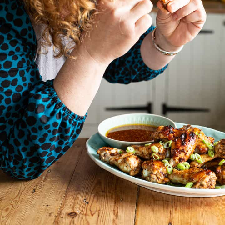 Woman hovering over a plate of hot chicken wings eating a piece of chicken