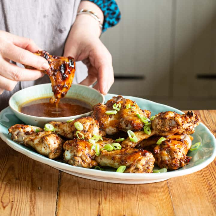 womans hands dipping a golden brown hot chicken wing into a small bowl of hot dipping sauce