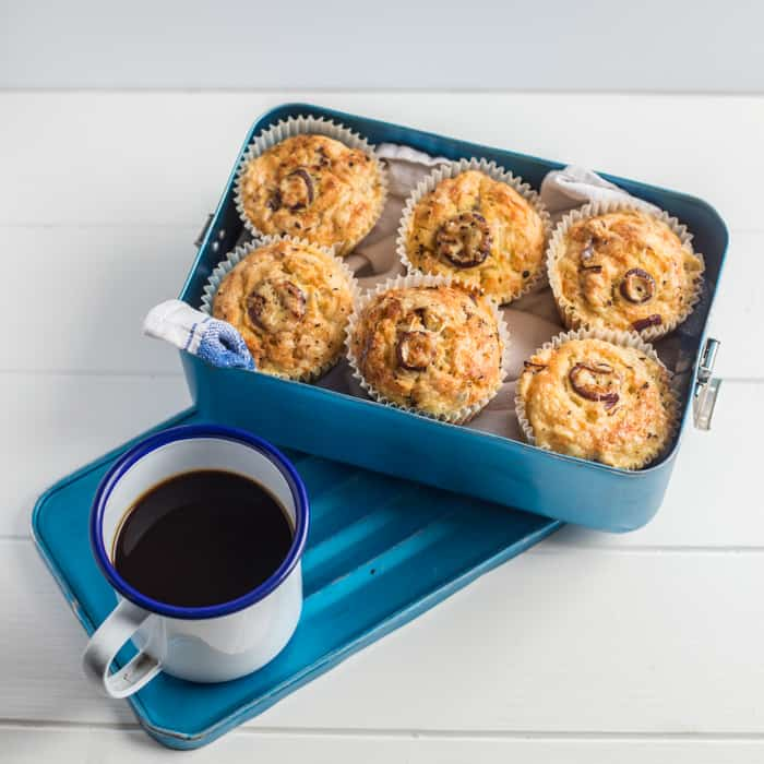 Cheese and Red Onion Muffins in a bluebox beside a mug of black coffee
