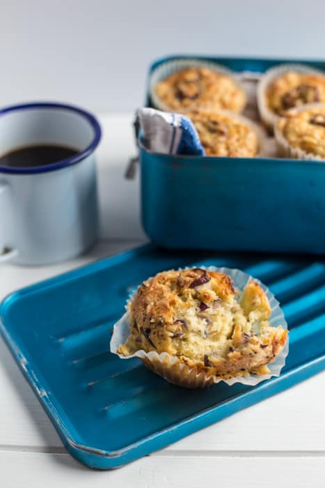 Cheese and Red Onion Muffins in a blue box beside a mug of black coffee witha half eaten muffin in the forground