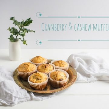 cranberry and cashew muffins on a plate against a white background with sprigs of holly