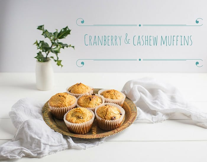 cranberry and cashew muffins on a plate against a white background with sprigs of holly, one of my 25 Homemade Christmas Gift Ideas