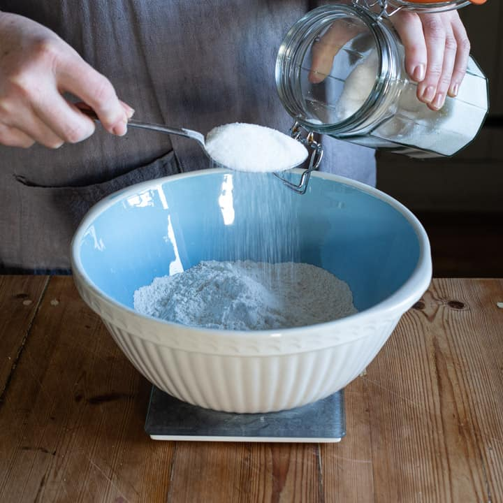 womans hands holding a metal spoon of sugar over a large blue and white mixing bowl