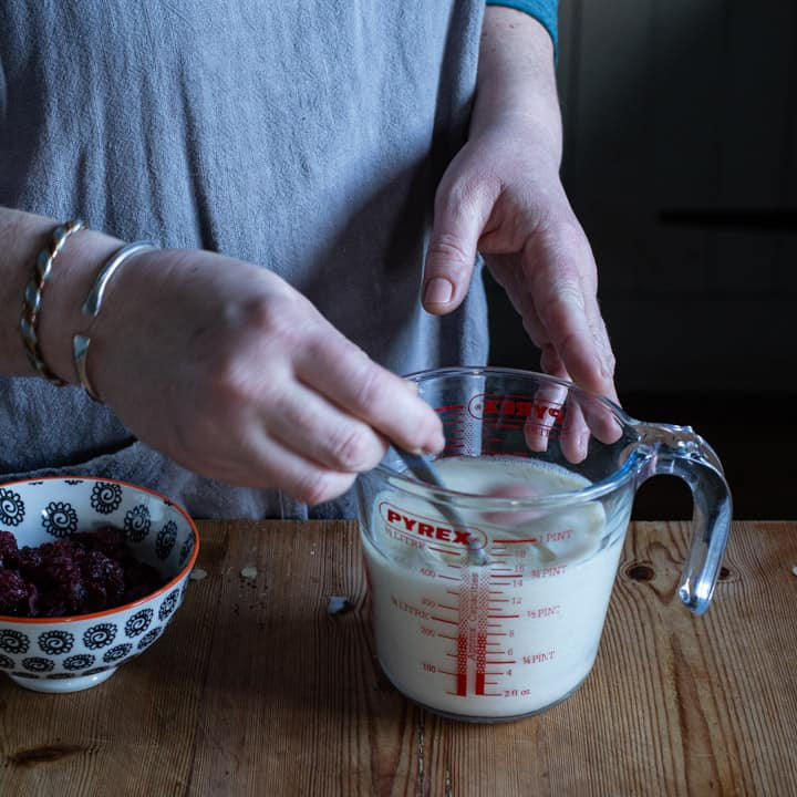 womands hands stirring the wet ingredients of a muffin recipe in a glass jug