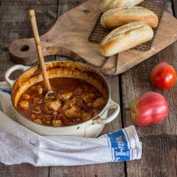 wooden backgrouns with white pan of chicken stew with chorizo and chickpeas