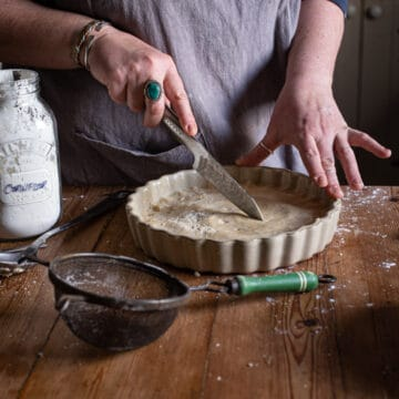 womans hands scoring shortbread in a flan dish on a wooden kitchen counter surrounded by baking mess