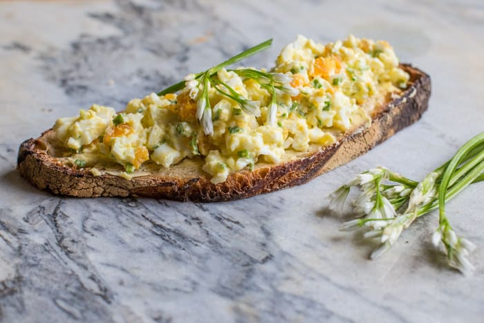 wild garlic egg mayo piled on crusty bread on a marble slab with wild garlic flowers