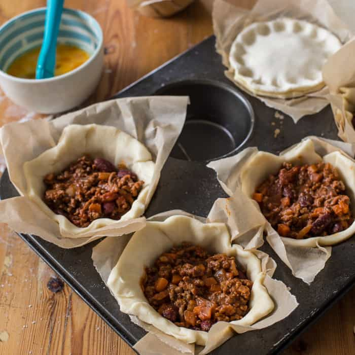 Chilli Beef Pies being assembled in a muffin tin on a wooden table surrounded by baking equipment