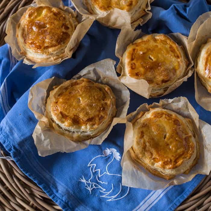 Chilli Beef Pies on a blue cloth in a wicker basket