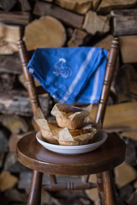 Chilli Beef Pies piled up on a white plate on a wooden chair with a blue cloth