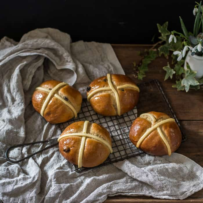 Dairy Free Hot Cross Buns on a cooling tray on a whitecloth with a vase of snowdrops
