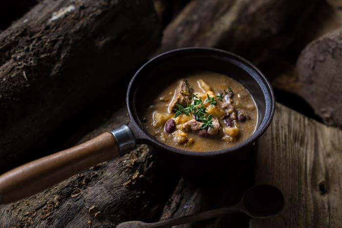 Slow Cooker Pepperpot Stew recipe cooked in a pan on a piece of wood