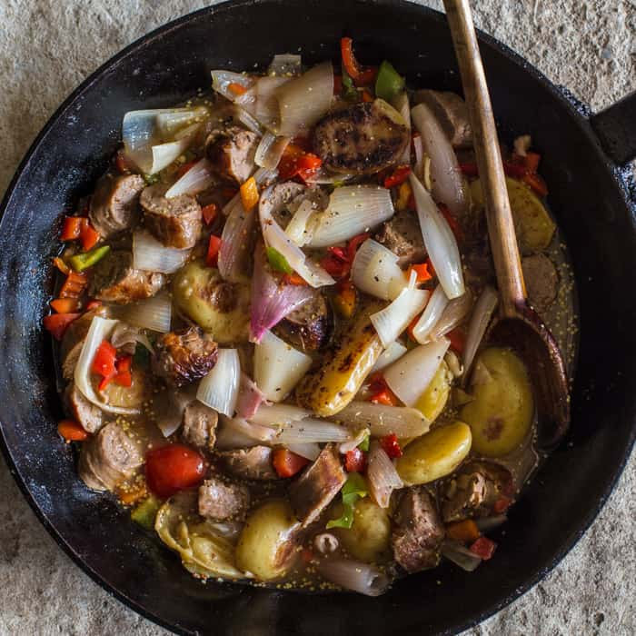 Sausage and Cider Campfire Skillet with a wooden spoon