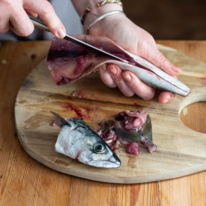 womans hands holding a mackerel and cutting it open to make sushi
