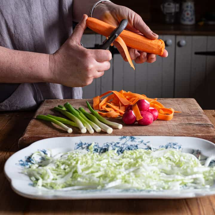 woman in grey grating a carrot over a bunch of other salad vegetables