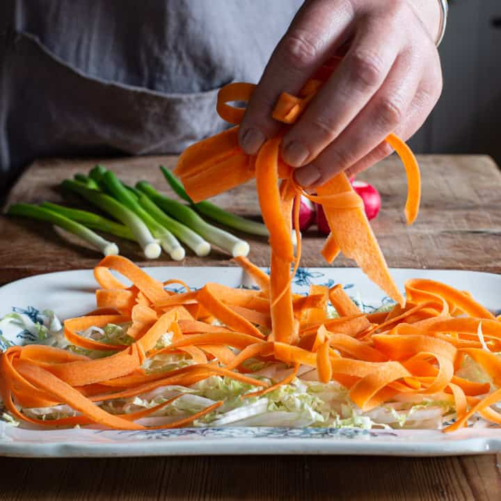 womans hand placing ribbon of peeled carrot onto a salad platter