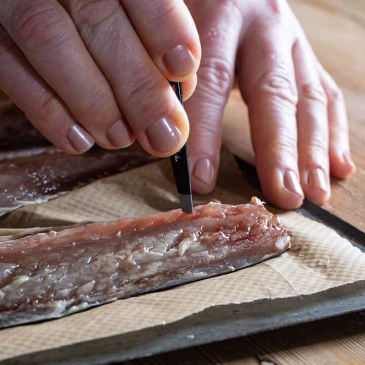 womans hands holding a pair of tweezers and pinching bones out of a fresh mackerel fillet