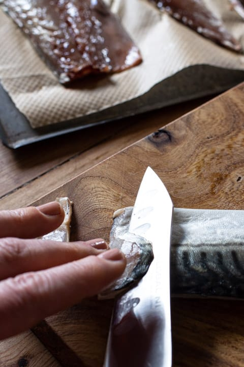 womans hands using a sharp silver knife to slice thin slices from a raw mackerel fillet