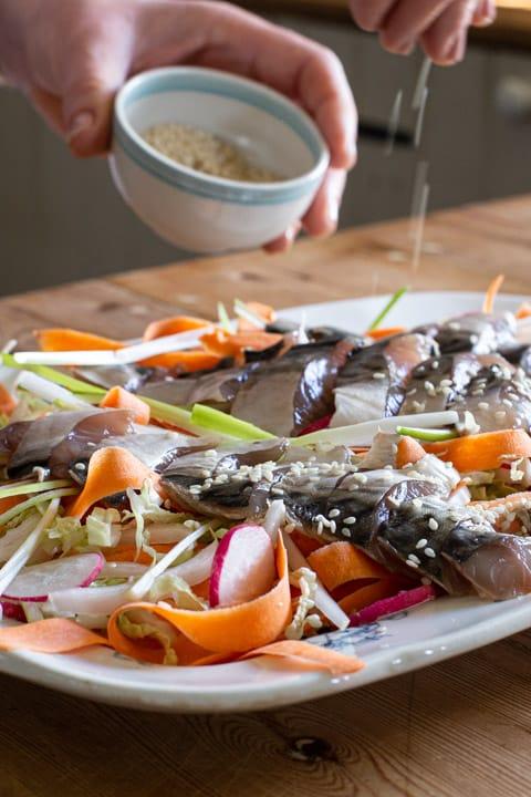 woman sprinkling sesame seeds onto a mackerel sashimi platter
