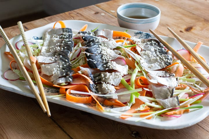 blue and white platter of salad and raw mackerel with chopsticks on the side