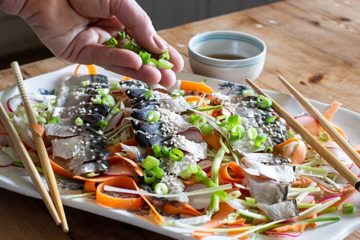 womands hands sprinkly chopped green onion onto a white plate of homemade sashimi salad