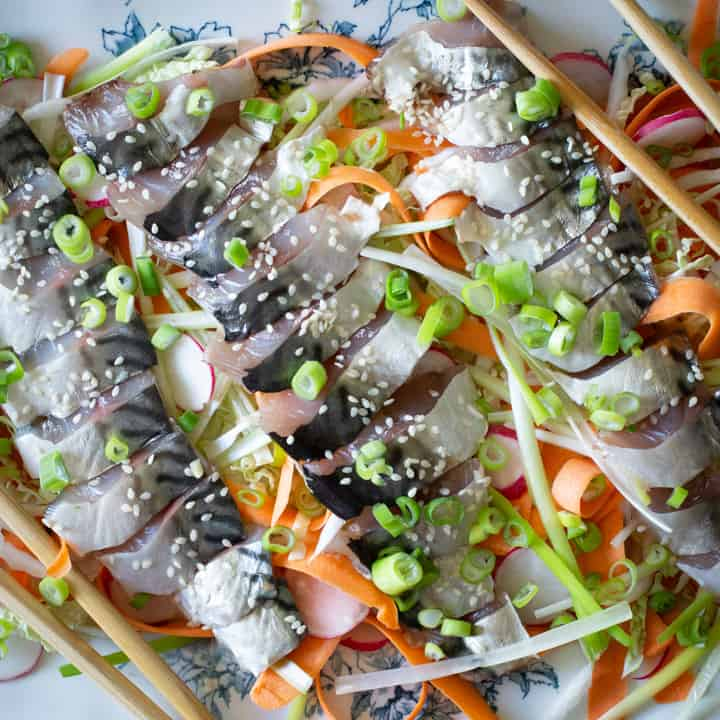 blue and white plate of raw fish sashimi salad, salad and chopsticks