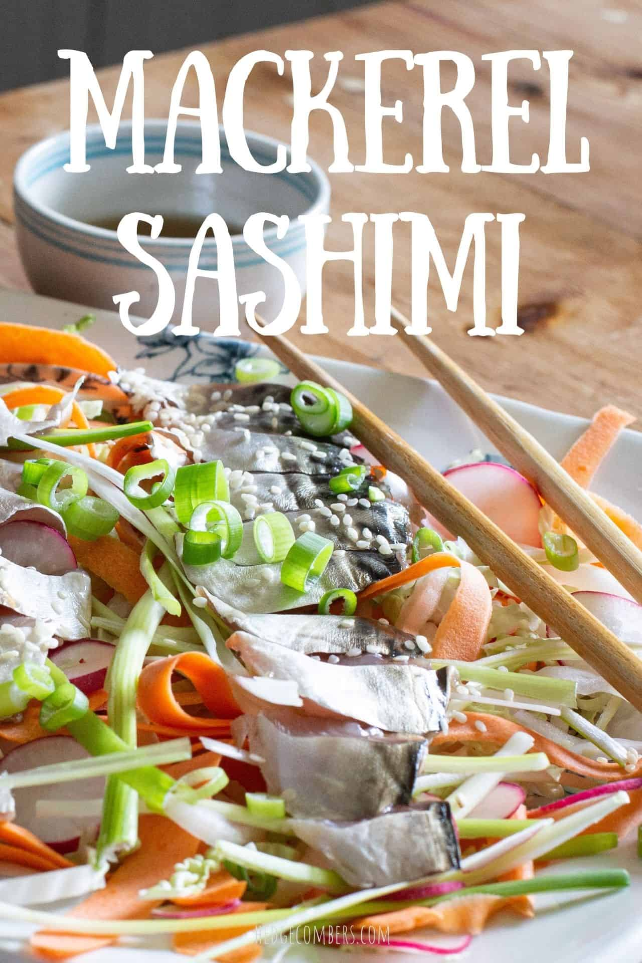 white plate on wooden surface topped with orange and green salad and a fillet of fresh mackerel sashimi sliced on top