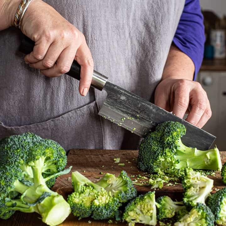 womans hands chopping fresh broccoli with Japanese knife on a wooden board