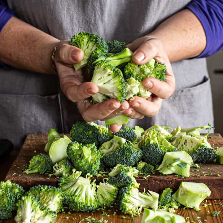 womans hands holding a handful of chopped broccoli over a woonden counter