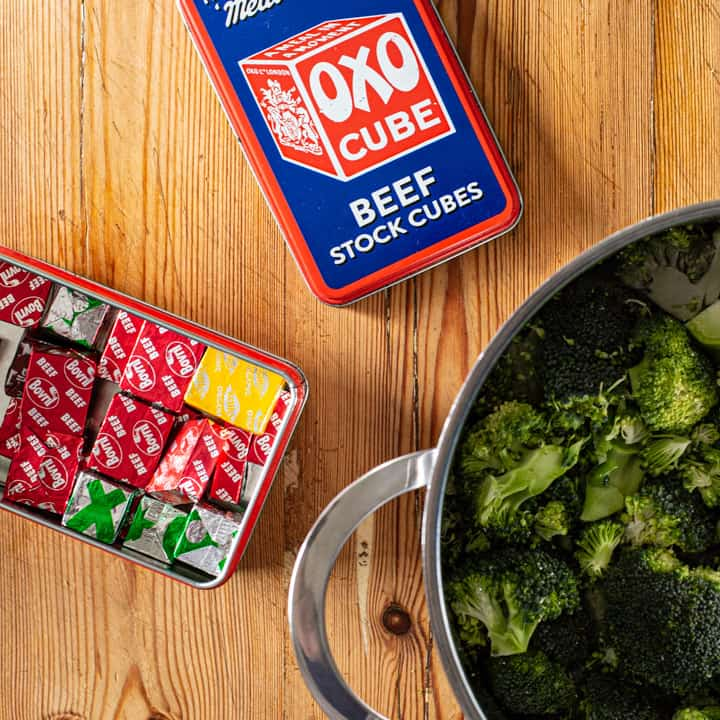 wooden kitchen counter with a range of stock cubes in a red tin and a saucepan of fresh broccoli