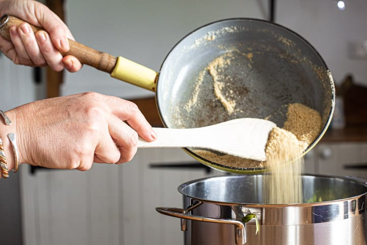 womans hands tipping toasted ground almonds from a frying pan into a stock pan of soup