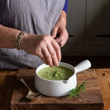 womans hands sprinkling fresh herbs on a bowl of bright green broccoli soup