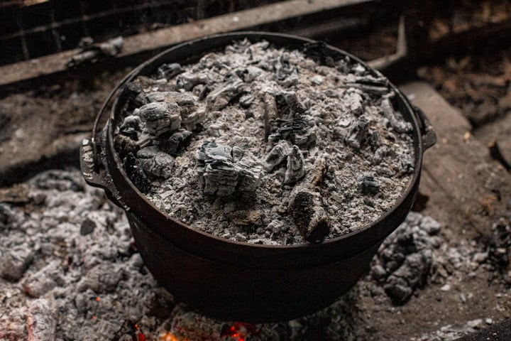 dutch oven sitting in campfire embers with more embers on the lid roasting a whole chicken
