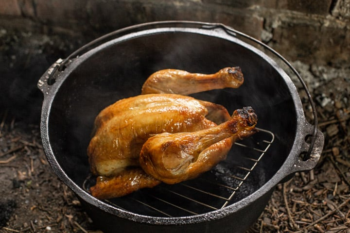 Golden brown roast chicken inside a cast iron dutch oven