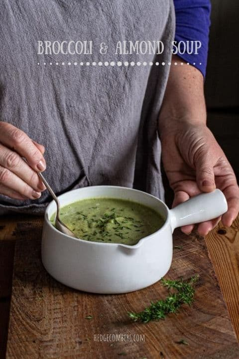 womans hands holding a soup spoon over a bowl of broccoli and almond soup on a wooden surface