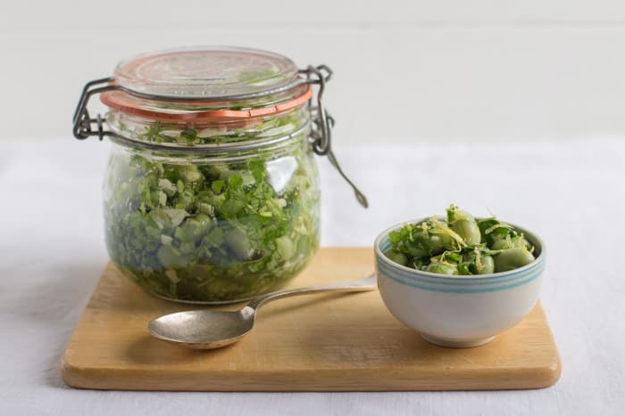 A kilner jar of Marinated Broad Beans beside a white bowl of beans and a spoon on a wooden board against a white background