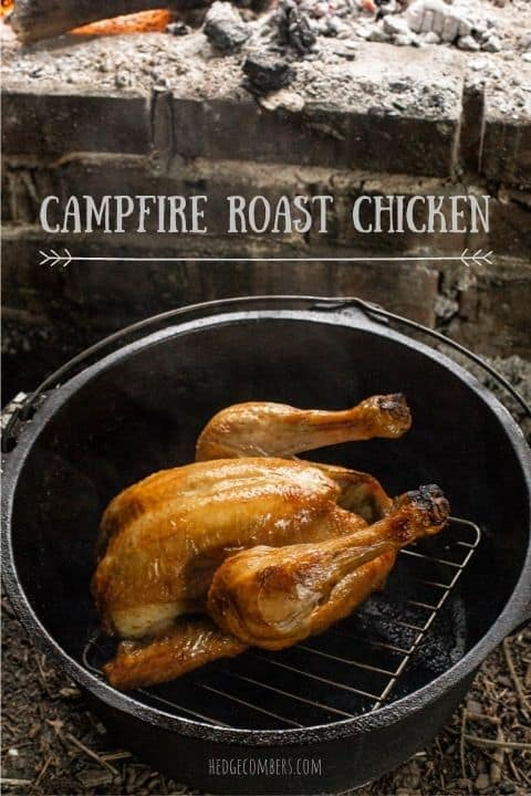 golden roasted chicken in a dutch oven next to a campfire