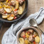 white bowl of hearty sausage and cider stew with a cast iron skillet in the background