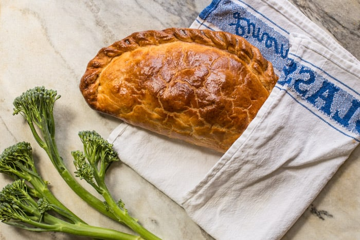 Tenderstem and Cornish Blue Cheese Pasty in a blue and white tea towel on a marble board with tenderstem along side