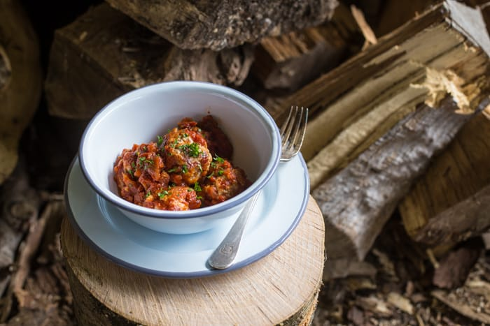 Spicy n'duja meatballs in a white bowl with a fork surrounded by pieces of wood