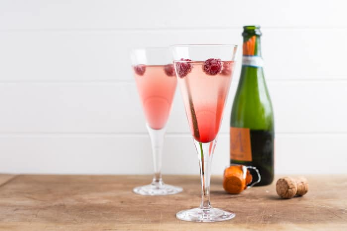 A bottle of Prosecco, 2 cocktail glasses with pink kir royale recipe in them and a cork