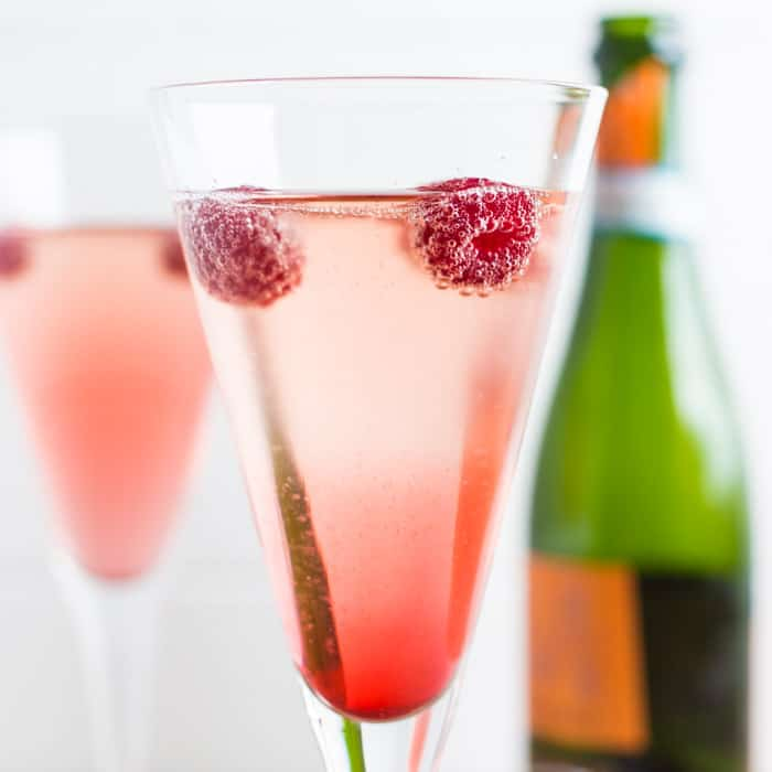 Raspberries floating on the surface of a glass of Kir Royale with prosecco