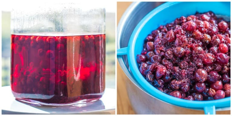 Homemade Blackurrant Cassis in a glass bottle alongside blackcurrants in a sieve
