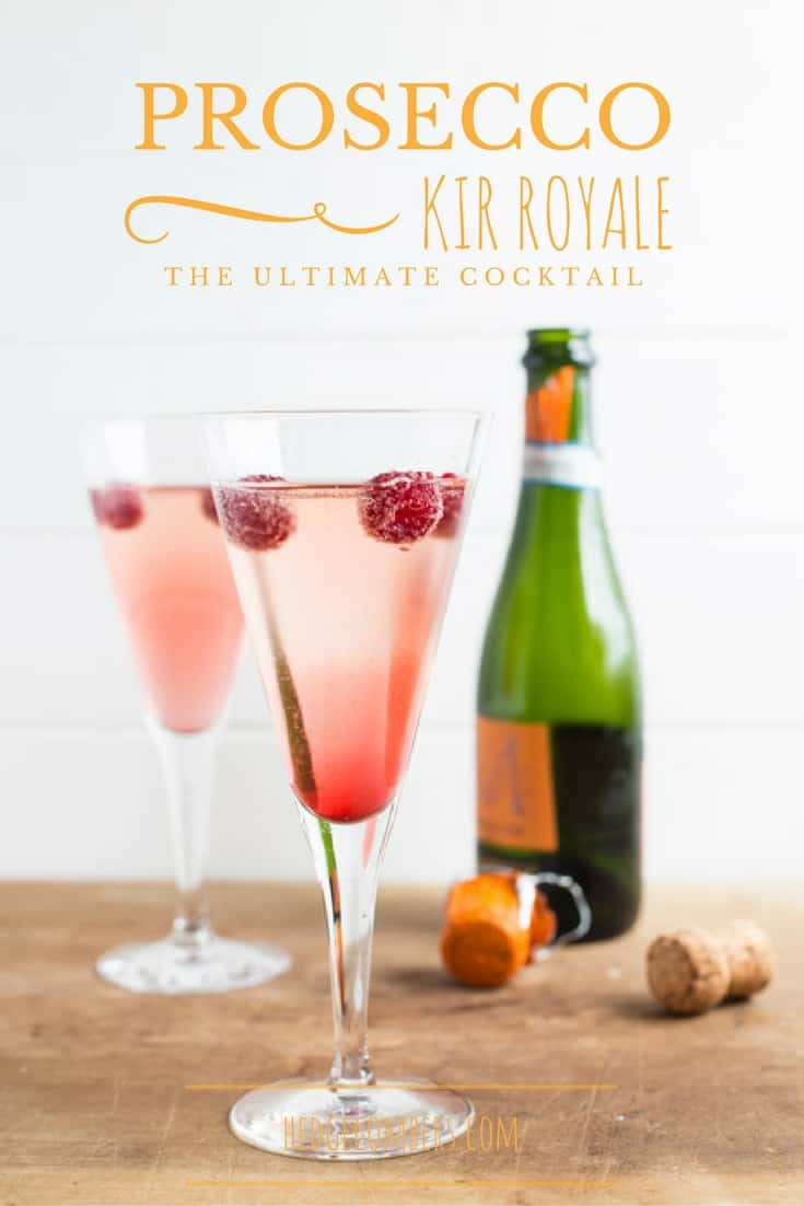 Prosecco bottle and glasses filled with pretty Kir Royale recipe and raspberries