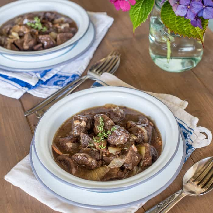 Slow Cooker Venison in Cider in blue and white bowls with spoons and forks on a table top