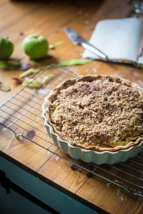Blackberry and Apple Crumble Pie in a pie dish on a cooling traysurrounded by baking ingredients and equipment