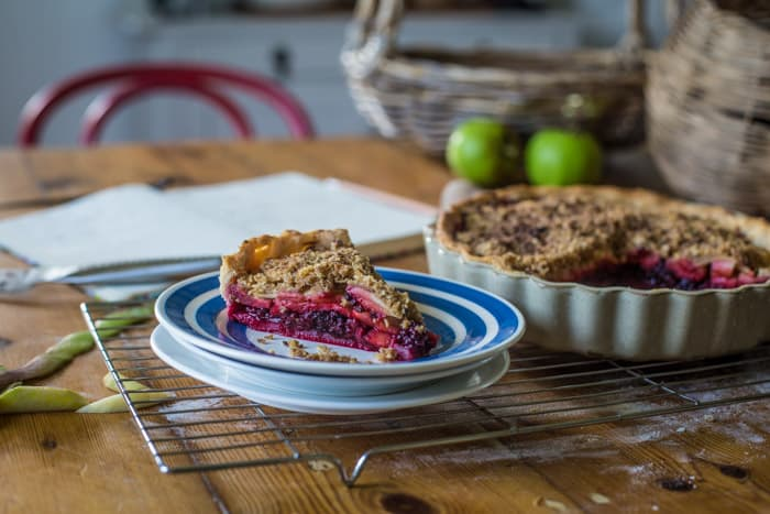 Blackberry and Apple Crumble Pie in a pie dish with 1 slice on a blue and white plate